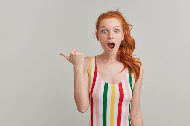 Geschokt, mooi roodharig meisje met paardenstaart en sproeten, gekleed in gestreepte kleurrijke zwembroek