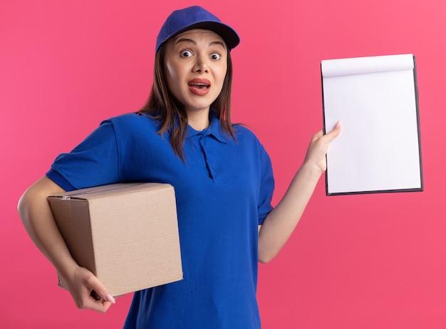 Geschokt mooie bezorgvrouw in uniform houdt kartonnen doos en klembord geïsoleerd op roze muur met kopie ruimte
