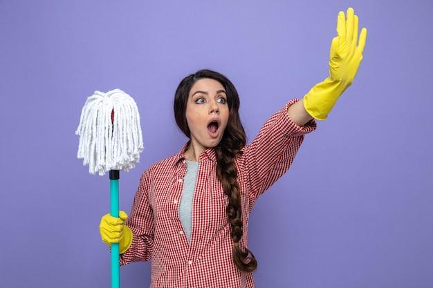 Geschokt mooie blanke schonere vrouw met rubberen handschoenen die menigte vasthoudt en gebarend stopbord kijkt naar de zijkant?