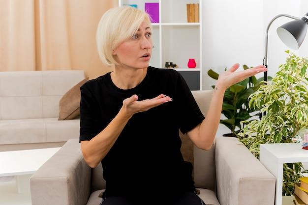 Geschokt mooie blonde russische vrouw zit op fauteuil kijken en wijzen naar kant met twee handen in de woonkamer