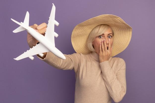 Geschokt mooie blonde slavische vrouw met strandhoed legt hand op mond en houdt modelvliegtuig op paars