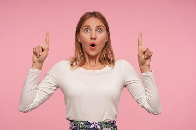 Geschokt mooie blonde vrouw met natuurlijke make-up op zoek naar camera met verbaasd gezicht, naar boven wijzend met wijsvingers en ronde ogen met opgetrokken wenkbrauwen, geïsoleerd op roze achtergrond