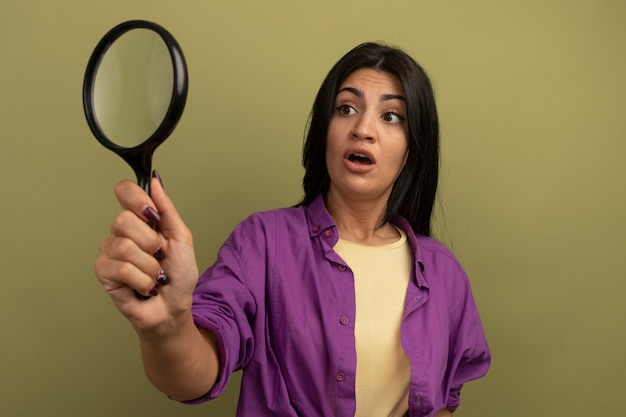 Geschokt mooie brunette blanke vrouw houdt en kijkt naar vergrootglas geïsoleerd