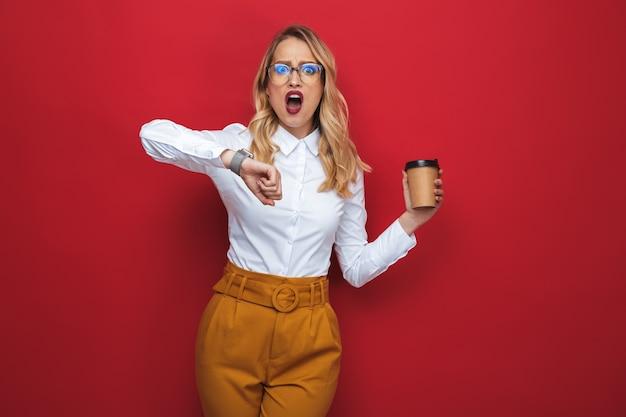 Geschokt mooie jonge blonde vrouw stond geïsoleerd op rode achtergrond, afhaalmaaltijden koffiekopje te houden, tijd te controleren