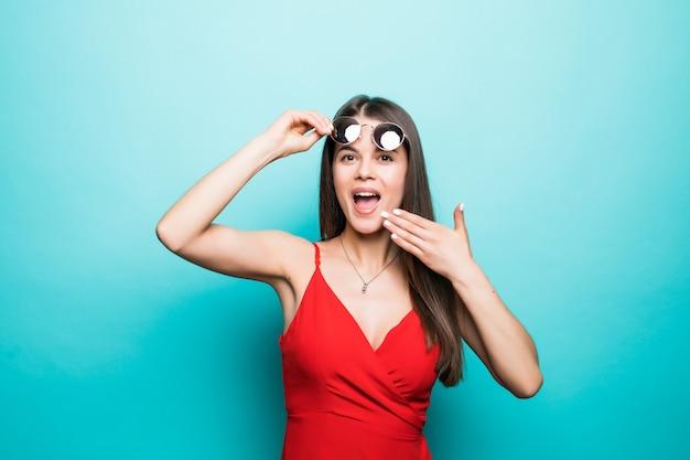 Geschokt mooie jonge vrouw in rode minikleding en zonnebril bedekken mond met hand op blauwe muur.