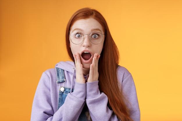 Geschokt onder de indruk roodharige vriendin laten vallen kaak hijgend schreeuwend wow omg wang dichtbij mond wijde ogen verbaasd reageren verbazingwekkend nieuws verse geruchten roddelen verbaasd, oranje achtergrond.