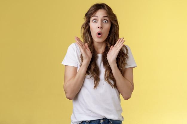 Geschokt onder de indruk verrast meisje leer interessant aangenaam goed nieuws klap handen open mond vouw lippen wow hijgend staren geïntrigeerd enthousiaste reactie geweldige prestaties gele achtergrond.