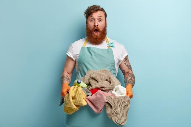 Geschokt onrustige roodharige bebaarde man in casual blauw schort, houdt bak met ongevouwen wasgoed