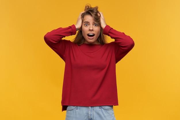 Geschokt ontevreden blond meisje kijkt verontwaardigd, mond wijd open, verstijfd van verontwaardiging, gekleed in een losse rode trui