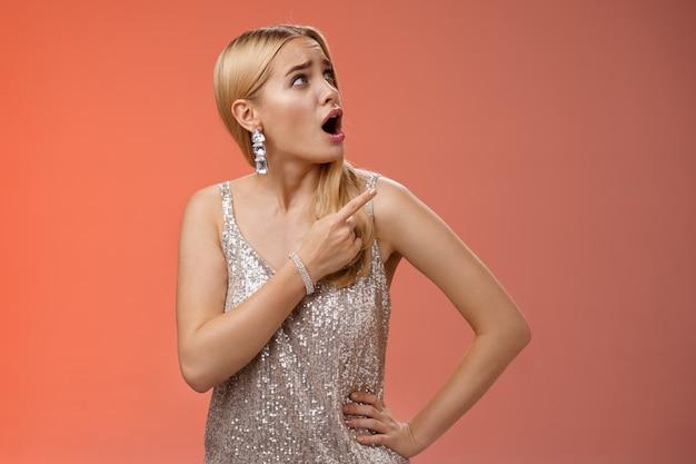 Geschokt ontevreden gehinderde arrogante blonde glamourvrouw in zilver glinsterende jurk draait rechterbovenhoek wijzend klaagend vreemd geluid naar boven, staande ondervraagde rode achtergrond.