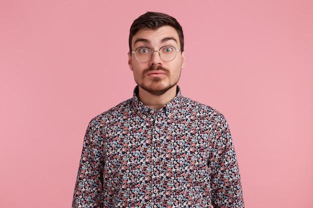 Geschokt onzeker verrast man staart door bril dragen kleurrijke shirt probeert situatie duidelijk te maken, over roze achtergrond