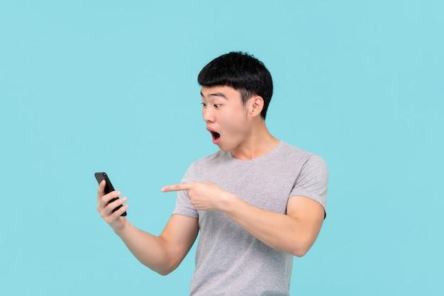 Geschokt opgewonden jonge aziatische man hijgend en wijzend naar mobiele telefoon