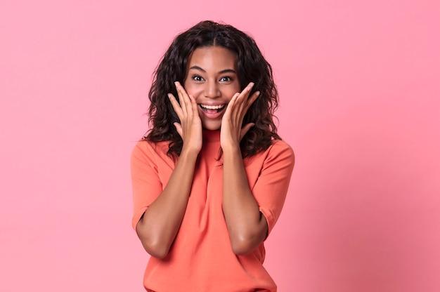 Geschokt opgewonden mooie afrikaanse vrouw met open mond op roze achtergrond