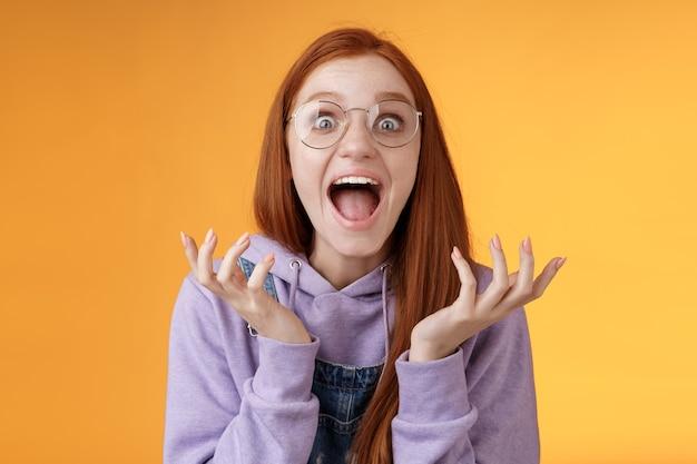 Geschokt opgewonden overweldigd jong schreeuwend gelukkig roodharig meisje met een bril die wint en hoort uitstekend nieuws schreeuwend hardop vreugde ongelooflijk geluk opstekende handen gespreid staren verrast.