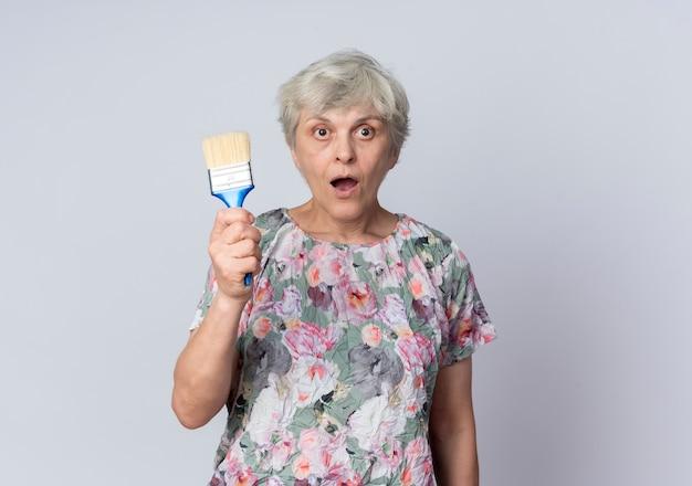 Geschokt oudere vrouw houdt verfborstel geïsoleerd op een witte muur