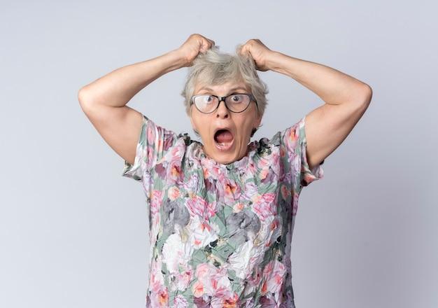 Geschokt oudere vrouw in optische bril houdt en heft haar op zoek geïsoleerd op een witte muur