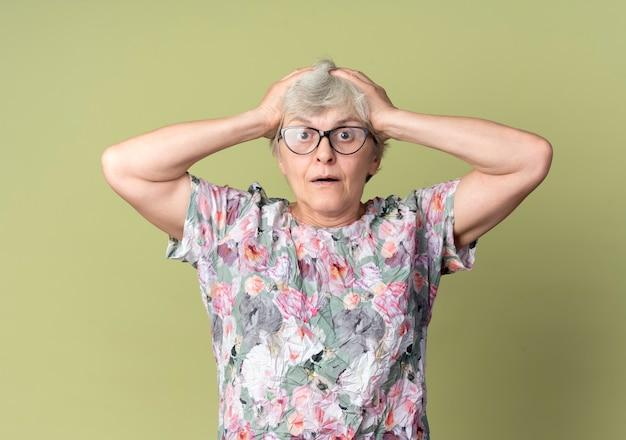 Geschokt oudere vrouw in optische bril houdt hoofd geïsoleerd op olijfgroene muur