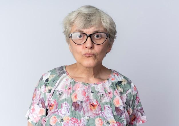 Geschokt oudere vrouw in optische glazen staat geïsoleerd op een witte muur