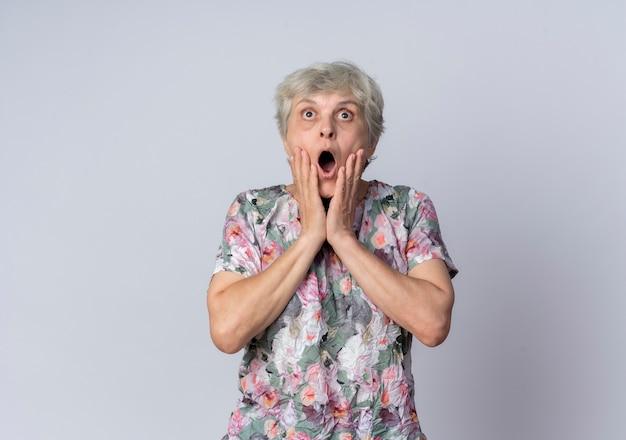 Geschokt oudere vrouw legt handen op gezicht kijkend uit geïsoleerd op een witte muur