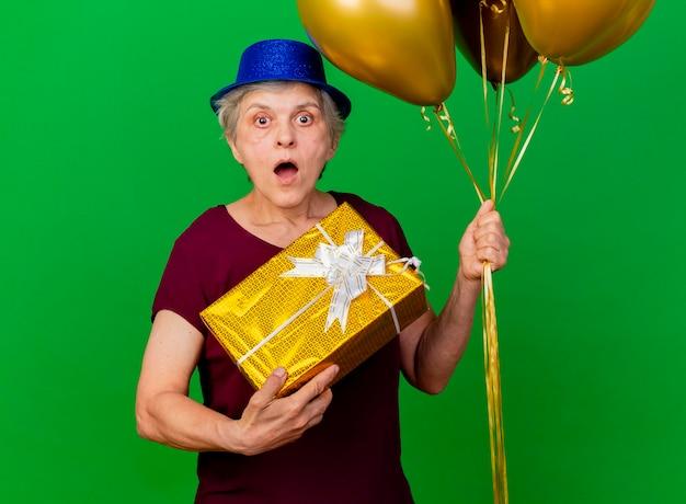 Geschokt oudere vrouw met feestmuts houdt helium ballonnen en geschenkdoos op groen
