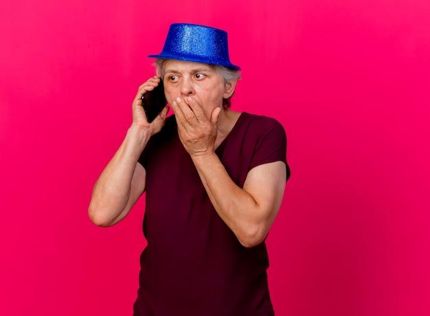 Geschokt oudere vrouw met feestmuts legt hand op mond praten aan de telefoon op roze