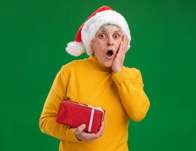 Geschokt oudere vrouw met kerstmuts legt hand op gezicht en houdt kerst geschenkdoos geïsoleerd op paarse achtergrond met kopie ruimte
