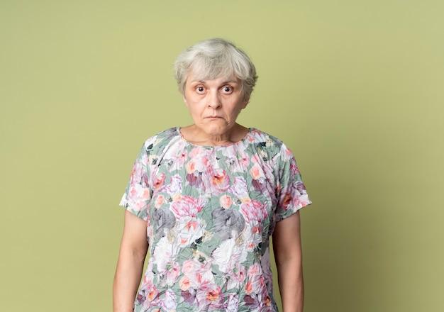 Geschokt oudere vrouw staat geïsoleerd op olijfgroene muur