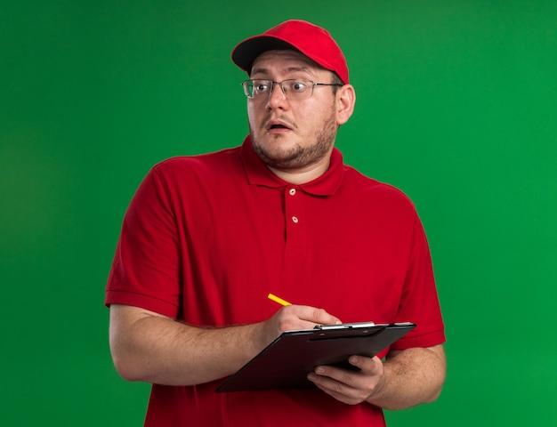 Geschokt overgewicht jonge bezorger in optische bril met klembord en potlood kijkend naar kant geïsoleerd op groene muur met kopieerruimte