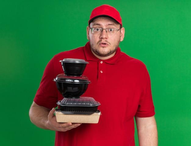 Geschokt overgewicht jonge bezorger in optische bril met voedselcontainers geïsoleerd op groene muur met kopieerruimte