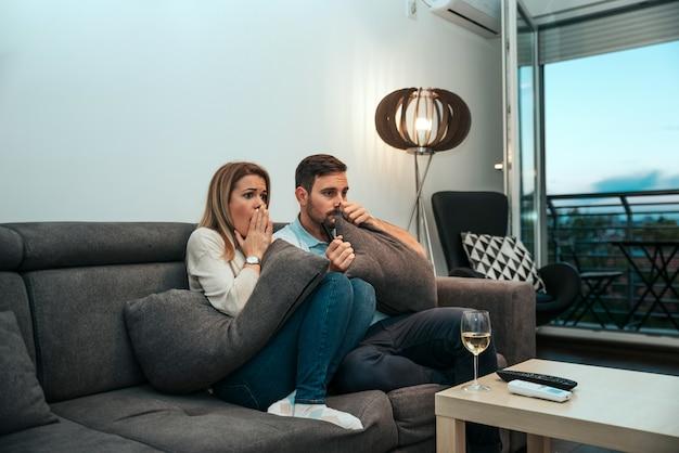Geschokt paar dat tv bekijkt.