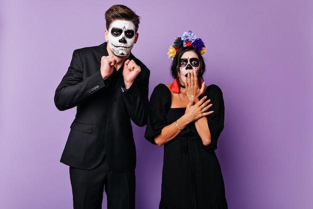 Geschokt paar met schedelvormige maskers in bang poseren op paarse muur. portret van een man in zwart pak en een meisje in een donkere jurk met heldere accenten.