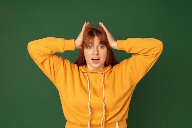 Geschokt. portret van een blanke vrouw geïsoleerd op groen met copyspace