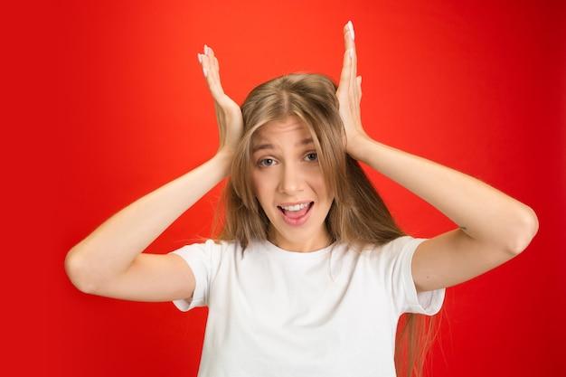 Geschokt. portret van jonge blanke vrouw met heldere emoties op rode studio achtergrond met copyspace. blond model. concept van menselijke emoties, gezichtsuitdrukking, verkoop, reclame, jeugd.