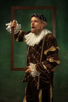 Geschokt. portret van middeleeuwse jonge man in vintage kleding met houten frame op donkere achtergrond. mannelijk model als hertog, prins, koninklijk persoon. concept vergelijking van tijdperken, modern, mode, verkoop.