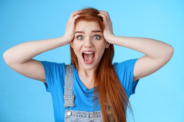 Geschokt roodharig meisje schreeuwt paniek, voelt zich onder druk staande deadlines, bang zie rotzooi, grijp het hoofd, schreeuw bang verontrust, staren camera hopeloos, angstig reageren verliezende loterij, blauwe achtergrond