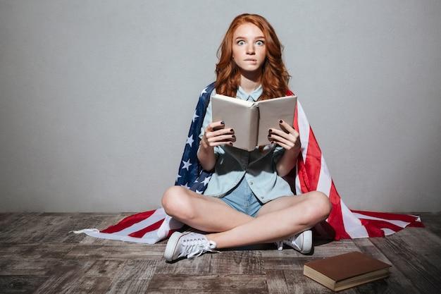 Geschokt roodharige jonge dame leesboek met vlag van de verenigde staten
