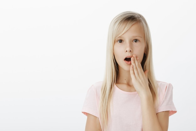 Geschokt schattig europees meisje met blond haar, geruchten of roddels verspreiden in de klas, palm bij de mond houden terwijl ze fluistert zodat niemand anders het geheim hoort, serieus over grijze muur staan