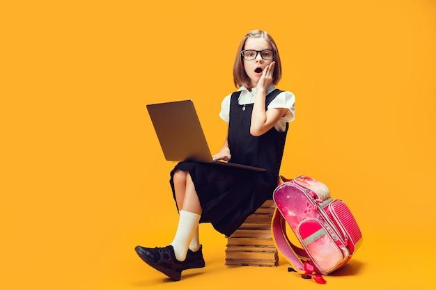 Geschokt schoolmeisje van volledige lengte zit achter een stapel boeken met pc, kijk naar het onderwijs van de camera voor kinderen