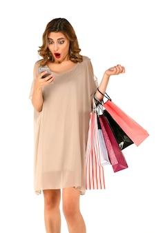 Geschokt shopper vrouw met boodschappentassen zag grote korting in app op slimme telefoon.