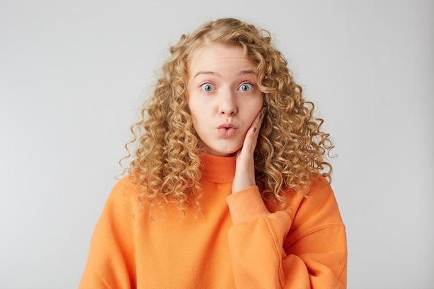 Geschokt starend blond meisje legt een hand onder ogen