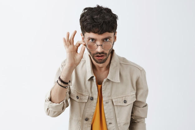 Geschokt stijlvolle bebaarde man poseren tegen de witte muur