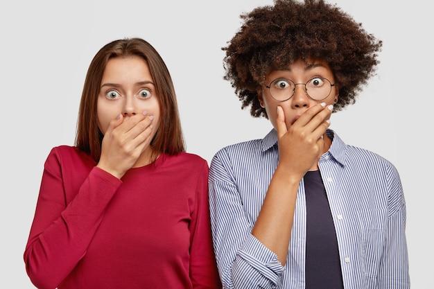 Geschokt stomverbaasde interraciale vriendinnen, handpalmen op de mond houden, stomverbaasd zijn, iets geheim houden