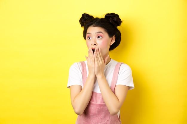 Geschokt tiener aziatisch meisje met make-up, hijgend en bedekkend mond, links kijkend naar verbaasd logo, staande op geel.
