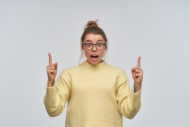 Geschokt tienermeisje met blond haar verzameld in een knot en tatoeage. gele trui en bril dragen. wijzende wijsvingers naar kopie ruimte. kijkend naar de camera, geïsoleerd over witte muur