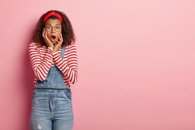 Geschokt tienermeisje poseren in overall met krullend haar