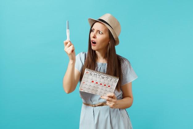 Geschokt trieste vrouw in blauwe jurk, hoed in de hand houden zwangerschapstest, periodekalender voor het controleren van menstruatiedagen geïsoleerd op blauwe achtergrond. medisch, gezondheidszorg, gynaecologisch concept. ruimte kopiëren.