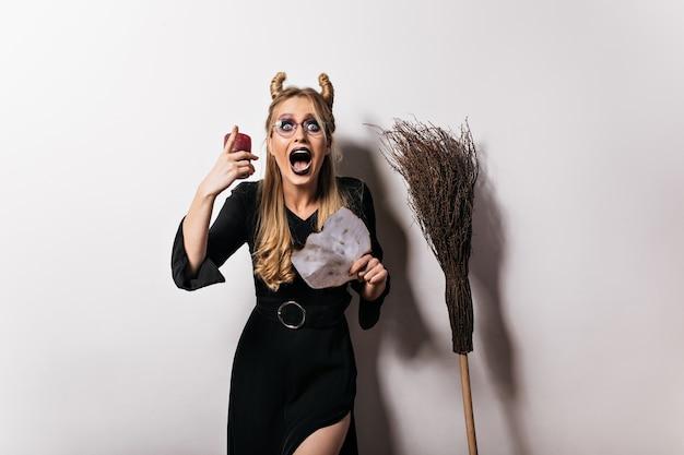 Geschokt vampiermeisje in glazen die verbazing uitdrukken. blij heks in lange zwarte jurk poseren in halloween.
