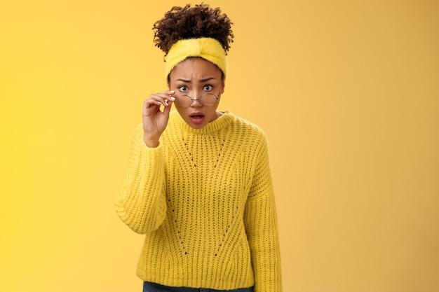 Geschokt verbaasd afro-amerikaanse vrouwelijke student drop kaak hijgend bezorgd verwarde take-off bril naar voren buigen geruststellen waarheid zien, staande onder de indruk sprakeloos, gele achtergrond.