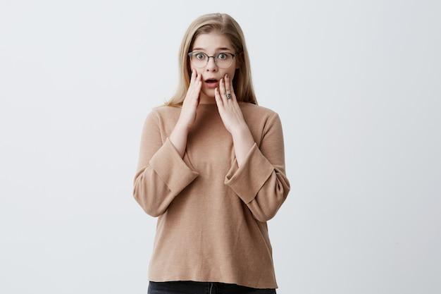 Geschokt verbaasd blonde vrouw die haar handen op wangen houdt en ogen laat knallen omdat ze in de war is, ontdekte schokkende informatie over haar vriendin. mensen, slecht nieuws, negatieve emoties
