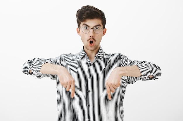 Geschokt verbaasd creatieve jonge kerel met snor in bril, naar beneden wijzend met wijsvingers, wauw zeggen en kaak laten vallen, iets geweldigs en verrassends naar beneden zien